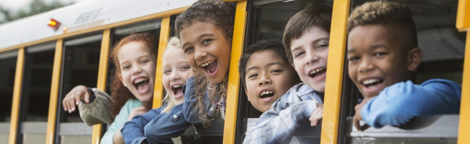 Children smiling with their heads out the bus windows